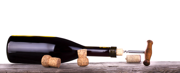 red wine and a bottle on a vintage wooden table isolated over white background